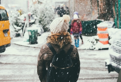 Woman in a brown winter jacket standing at the cornery of a snow-covered road. (Photo: Joseph Pearson/Unsplash)