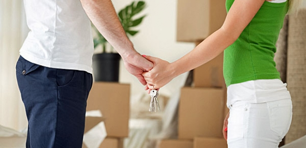 A man and woman holding hands and a set of keys with stacks of boxes and a plant in the background. (Photo: iStock Photo)