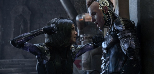 Alita (Rosa Salazar) has Zapan (Ed Skrein) pinned against a wall about to punch him. (Photo: 20th Century Fox)