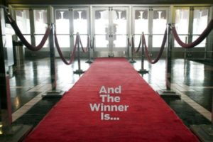 "A red carpet ropped off on the side with velvet ropes in a theater lobby with ""And The Winner Is..."" written on the carpet. (Photo: DC. Film Society)"