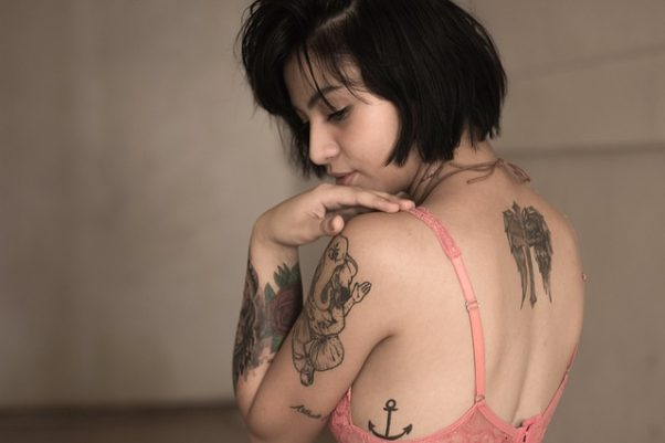 A woman in pink bra looking oer her shoulder with tattoo on back, side, shoulder and forearm. (Photo: Free-Photos/Pixabay)