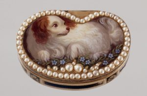 A small metal box with the lid outlined in pearls with a dog painted on it. (Photo: Hillwood Estate, Museum & Gardens)
