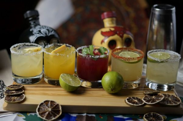 five different flavors of margaritas on a cuttting board with a bottle of tequila shaped like a skull behind them. (Photo: MXDC)