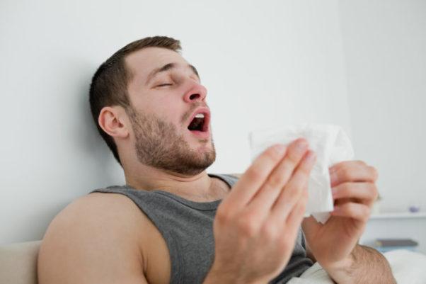 Sick man sneezing in his bed. (Photo: Deposit Photos)