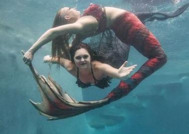 Two mermaids swim underwater. (Photo: Melanie Canatella)
