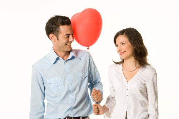 A man handing a woman a heart-shaped balloon. (Photo: Getty Images)