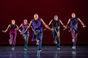 Five members of the Alvin Ailey Dance Theater perform on stage. (Photo: Alvin Ailey Dance Theater)