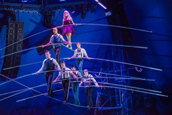 Seven tight rope walkers walk in pyramid formation balancing on each other across the tight rope. (Photo: Big Apple Circus)