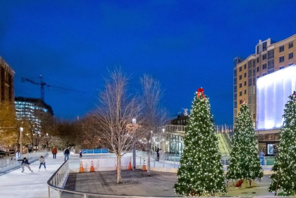 Skaters on the ice at the Canal Park Ice Skating Rink  with lit Christmas trees in the foreground. (Photo: Sam Kitner)