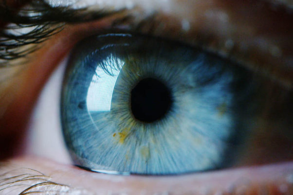 A close-up of a blue eye with flecks of green in it. (Photo: Shutterstock)