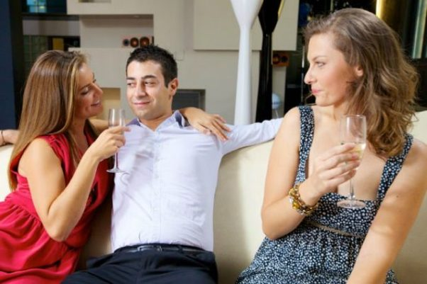 A man and woman sitting on a couch with arm around each other while another woman looks on unapprovingly. (Photo: Getty Images)