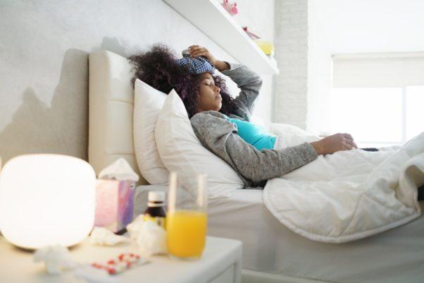 Black woman with flu and cold in bed holding an ice bag to her head. (Photo: Deposit Photos)
