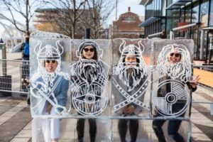 Four people standing beind likensses of vikings carved in ice with just their faces visible through a cutout at Yards Park. (Photo: Kaz Sasahara)