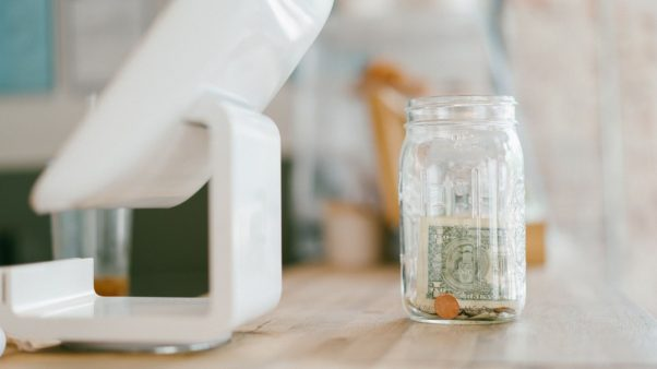 Electronic cash register screen with tip jar sitting on a wooden counter. (Photo: Kody Gautier/Unsplash)