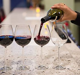A woman's hand pouring red wine into a glass. (Photo: Bastille)