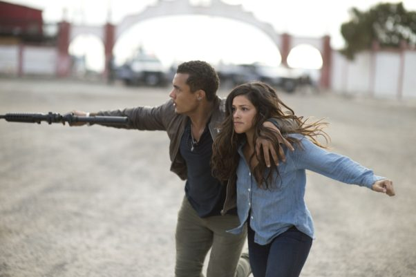 Ismael Cruz (left) holding a gun takes Gina Rodriguez hostage. (Photo: Sony Pictures)