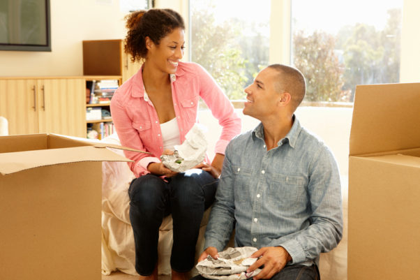 Mixed race couple unpacking boxes in new home. (Photo: Shutterstock)