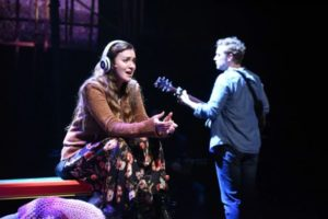 Girl sits singing with headphones on while Guy plays the guitar. (Photo: Stan Barouh)