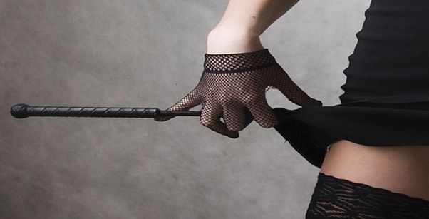 A woman in black lingerie and gloves holding a leather riding crop. (Photo: joshuatk/Pixabay)