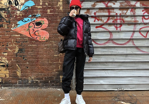 Wonan in black sweatpants and a red sweatshirt with a red beanieand black coat in front of a wall with graffitti. (Photo: devonleecarlson/Instagram)