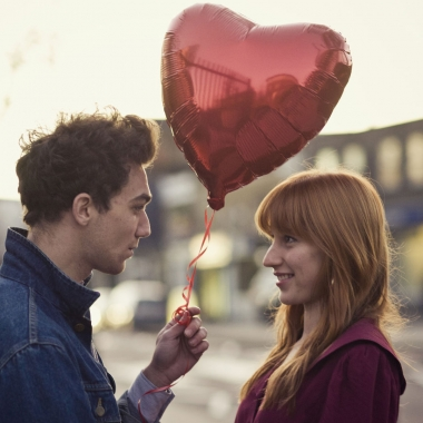 A man hainding a woman a heart-shaped balloon. (Photo: Getty Images)