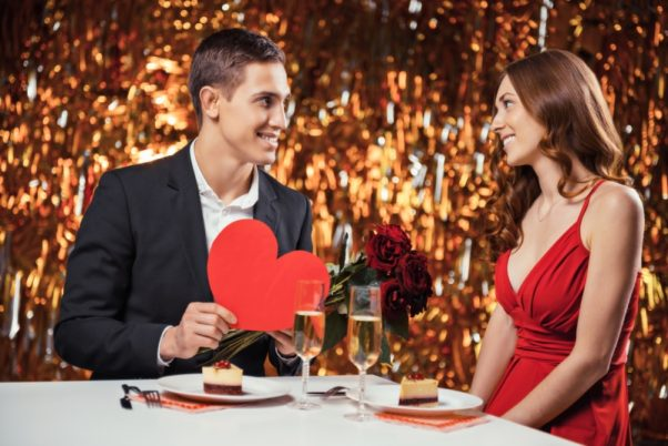 Man and woman at dinner having dessert and champagne with man holidng a red paper heart. (Photo: Alamy)
