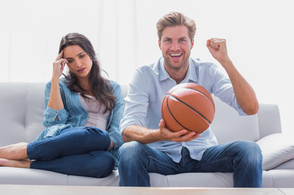 A man and woman watching a basketball game on TV. She looks disinterested while he is cheering and holding a basketball. (Photo: Shutterstock)