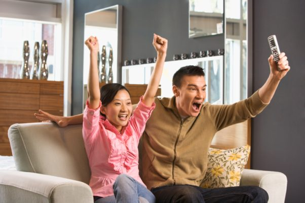 Asian woman and man on a couch watching sports on TV and cheering. (Photo: Shutterstock)