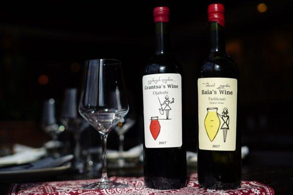 A bottle of Gvantsa's Wine Ojaleshi 2017 and Baia's Wine Tsolikouri 2017 sitting beside three empty wine glasses. (Photo: Supra)