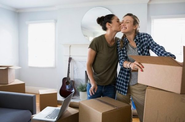 Two woman kiss on the cheek as they pack to move. (Photo: Alamy)