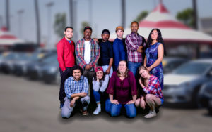 The cast of Hands on a Hard Body posing in front of a car lot. (Photo: Keegan Theatre)