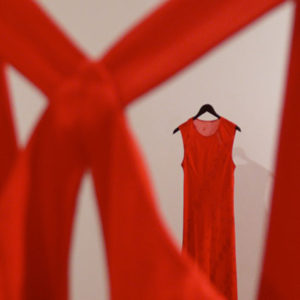 Empty red dresses haing on a wall. (Photo: Suzanne Morisette)