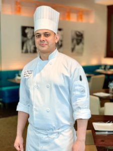 Photo of Rakesh Singh standing in the Rasika West End dining room. (Photo: Ashlie Levy)