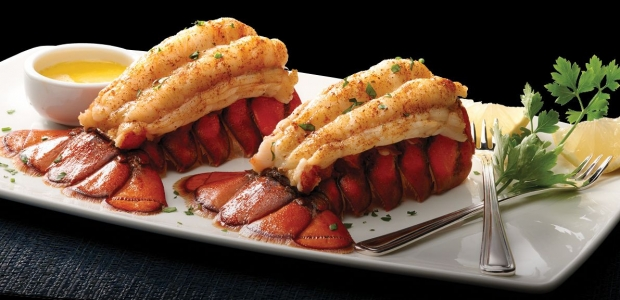 Two lobster tails on a white rectangle plate with drawn butter on the left and lemon and a fork on the right. (Photo: Morton's)
