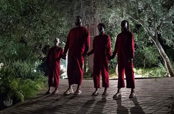 """Evan Alex as """"Pluto,"""" Winston Duke as """"Abraham,"""" Lupita Nyong'o as """"Red"""" and Shahadi Wright Joseph as """"Umbrae"""" dressed in red jumpsuits holding hands in a driveway. (Photo: Universal Pictures)"""