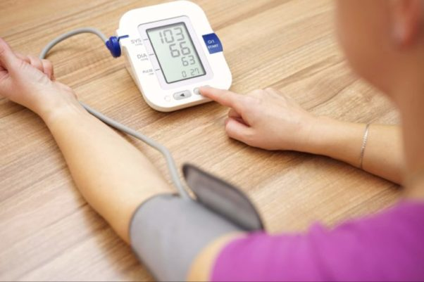 A woman taking her blood pressure with a digital readout. (Photo: Shutterstock)