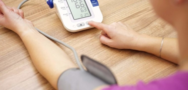 A woman taking her blood pressure with a digital readout. (Photo: iStock Photo)