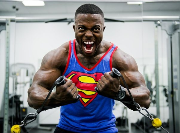 An African American male bodybuider in a Superman tank exercising his arms. (Photo: skeeze/Pixabay)