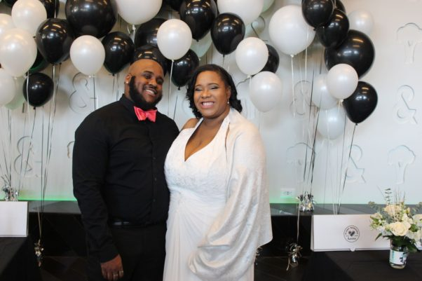 Adonis Miller and Jordan Monroe (l to r) stand in front of black and white balloons after their wedding. (Photo: Mark Heckathorn/DC on Heels)