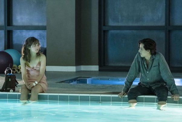 Stella (Haley Lu Richardson) and Will (Cole Sprouse) sit five feet apart with their feet in a pool. (Photo: CBS Films)