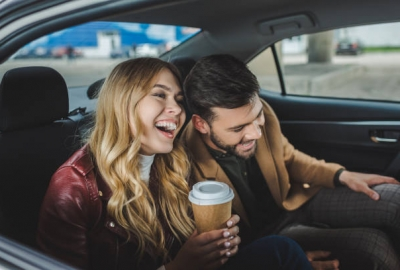 A happy young couple laughing while sitting together in taxi. (Photo: Shutterstock)