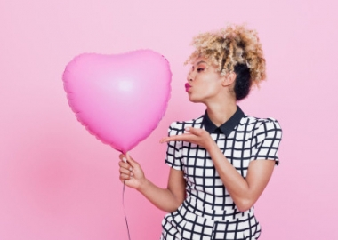 Young woman with big pink heart balloon. (Photo: Getty Images)