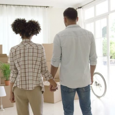 An African American couple holding hands looking at a pile of moving boxes. (Photo: Shutterstock)
