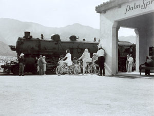 People on their bikes waiting as an old steam locomotive pulls into the Palm Springs train station. (Photo: Palm Springs Historical Society)