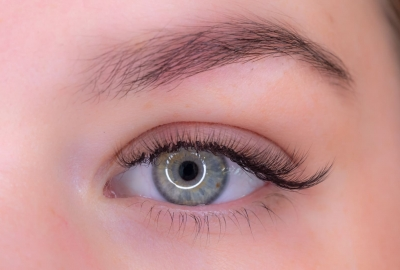 A close up of a green eye with long, thick lashes. (Photo: The Lash Spa)