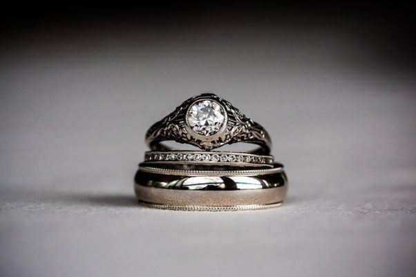 A woman's enagement ring, wedding ring and a man's wedding ring piled on top of one another. (Photo: durugby2005/Pixabay)