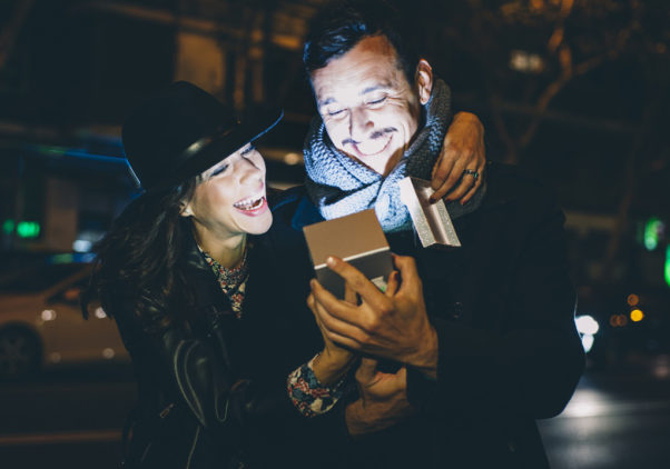 A man and woman looking at a cell phone laughing. (Photo: fiveprime.com)
