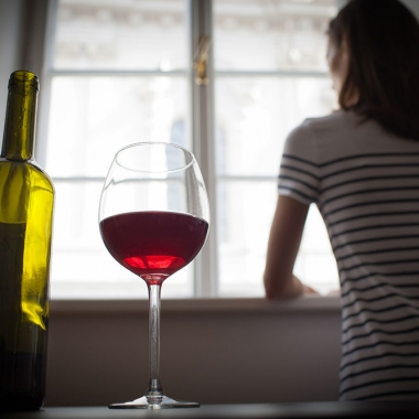 A woman stares out a window. Behind her, in the foreground, a glass of wine sits next to a bottle. (Photo: Getty Images)