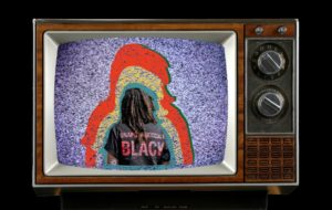"""A black man from behind on an old dial TV with """"Unapologetically Black"""" on the back of his shirt. (Image: Hirshhorn Museum)"""