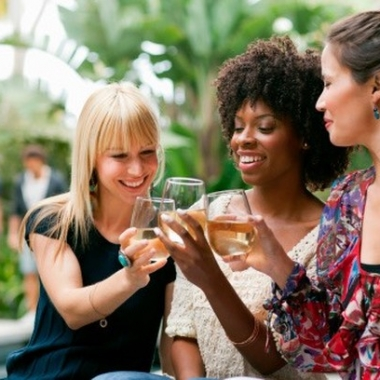 Three women friends sitting in a garden making a toast. (Photo: PicBon)